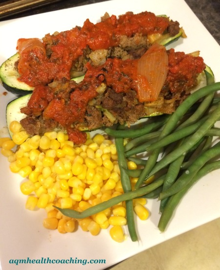 Ground Beef, onion and fennel stuffed Zucchini boats, topped with homemade fast marinara sauce and served with organic corn and steamed green beans